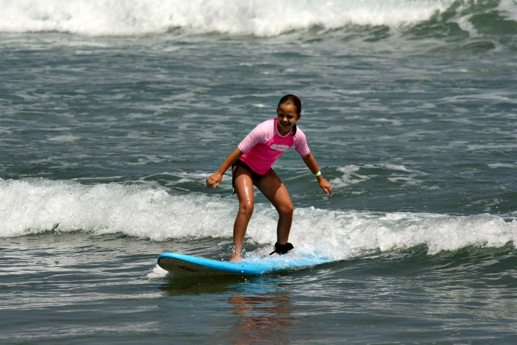 Teenage girl surfing on a blue surfboard at Aloha Beach Camp's Los Angeles, CA surf camp program