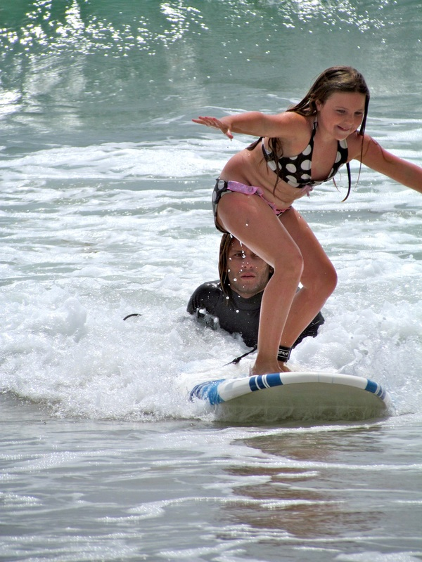 Girl surfing as her surf instructor looks on at Ballona Beach Summer Camp in Los Angeles