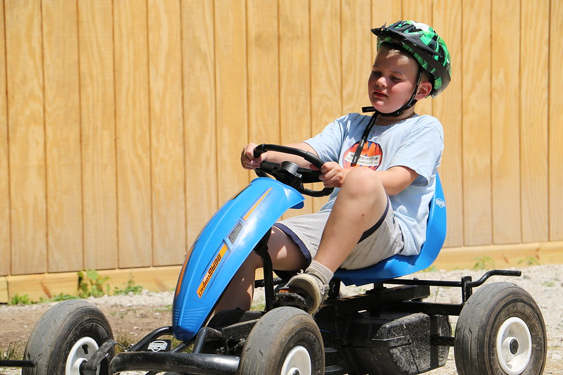 Boy riding a go-cart at summer camp