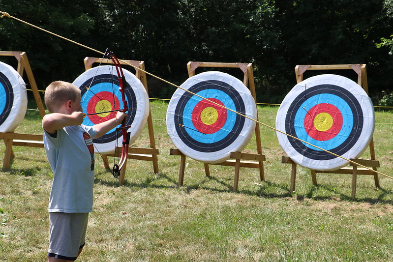 Boy doing archery at day camp