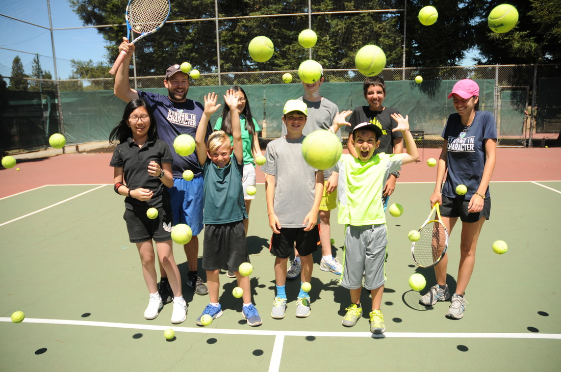 JCC Maccabi Sports Camp kids with counselors standing on tennis court throwing tennis balls into air and laughing.