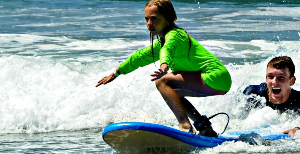 Kahuna camper surfing in the ocean with camp counselor holding her surfboard for support at Aloha Beach Camp, Los Angeles