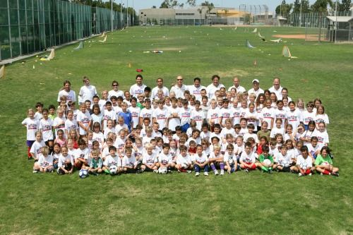 Full camp photo, at least 100 campers and staff, sitting together on the ballfield at Brit West Soccer Camp.