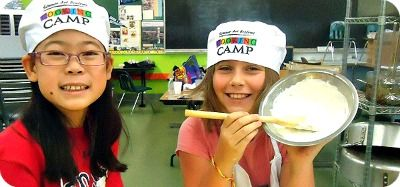 Two girls in a kitchen wearing cooking camp chef hats
