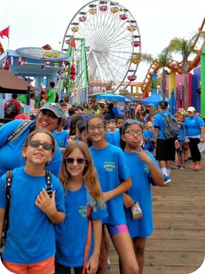 Group of female campers with their camp counselor standing together on the Santa Monica Pier
