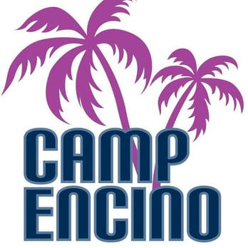 Two boys standing side-by-side wearing swimming goggles and wearing their blue Camp Encino camp t-shirts.