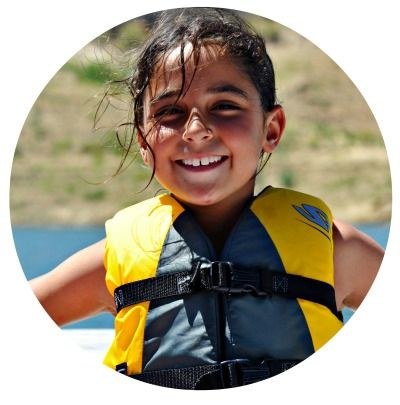 Girl wearing a lifevest sitting on a boat at summer camp and smiling.
