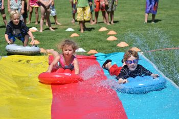 A boy and a girl having fun on a Slip-n-Slde at Camp Funtime in Encino.