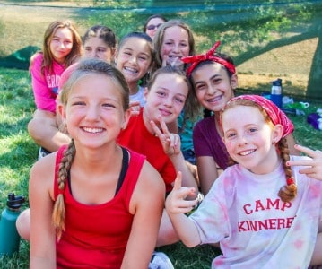 Group of girls at Camp Kinneret Summer Day Camp sitting on a ballfield.