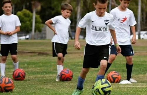 Four boys kicking soccer balls on a ballfield at Elite Soccer Training Summer Camp in Encino.