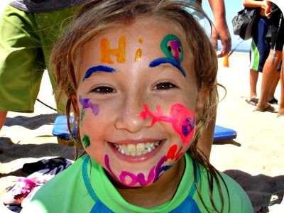Little girl with her face painted sitting on the beach at summer camp.