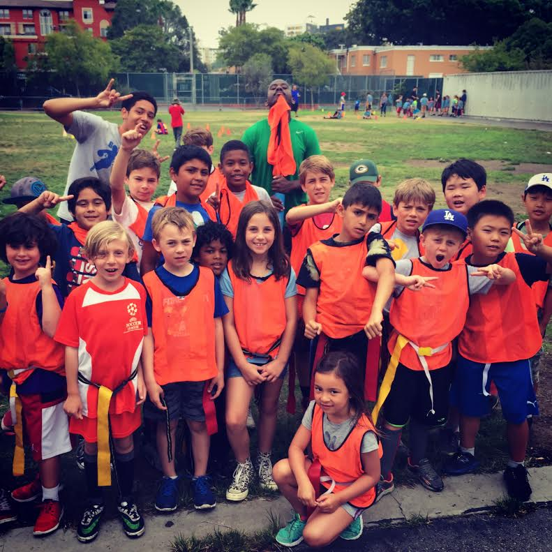 Kids wearing orange sports vests getting ready to play flag football at Got Game Summer Camp in Los Angeles