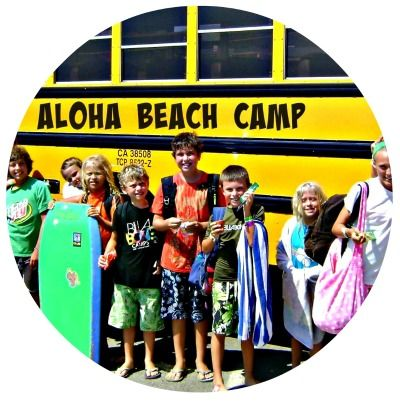 Aloha Beach Camp summer camp bus with campers lined up outside ready to board the bus.