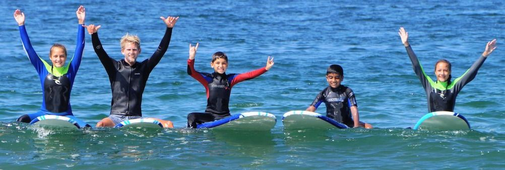 Five kids in the ocean sitting on their surfboards with hands up in the air at Learn to Surf L.A. summer camp