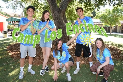 Five camp counselors under a tree posing together at Camp Los Encinos