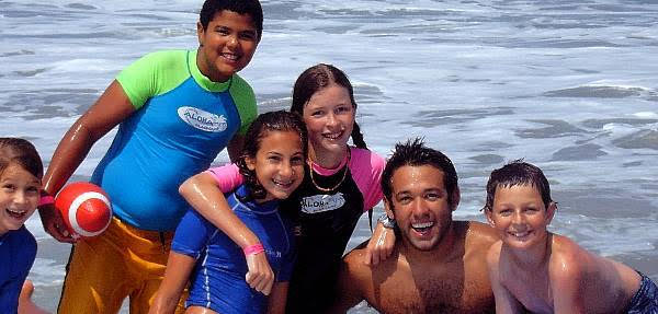 5 kids from Thousand Oaks attending Aloha Beach Camp hanging out with their camp counselor in the Ocean