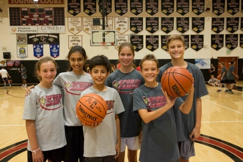 Six campers (three boys and three girls) standing together in the gym holding basketballs at Oaks Christian Summer Sports Camp