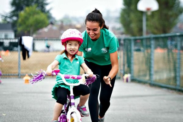 Female camp counselor at Pedelheads Bike Camp in Los Angeles teaching a young camper how to ride a bike.