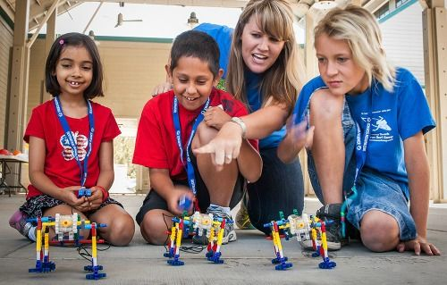 Three campers and their camp counselor building and racing robots at Destination Science Summer Camp