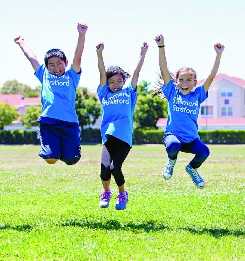 Three kids jumping for joy on a grass ball field at Summer at Stratford Day Camp