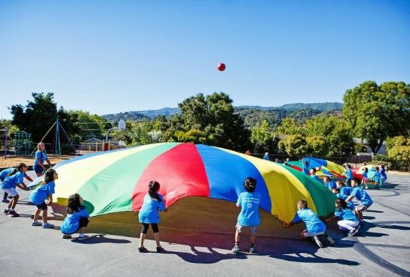 Large group of campers playing with a parachute and ball at Summer @ Stratford summer camp in L.A.