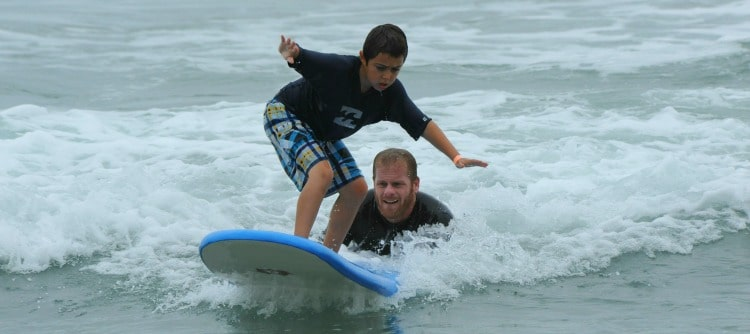 Boy receving surfing instruction from his camp counsleor while enjoying his Los Angeles surf camp experience at summer camp.