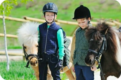 Two children standing next to horses at Traditional Equitation School summmer camp