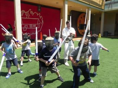 Campers having fun on the ballfield holding swords and lightsabers at Village School Summer Camp in the Pacific Palisades